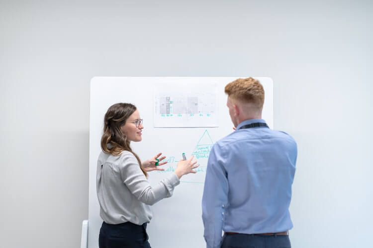 engineer discusses data in meeting with colleague